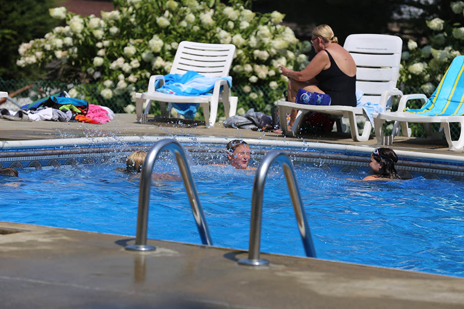 kids playing in the pool with woman sitting on lounge chair